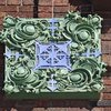 Detail, green and blue glazed terracotta corner ornament, second story arcade